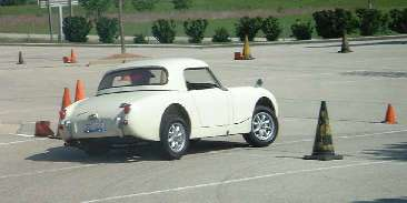 white Healey bugeye running the cones